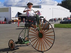 WAAAM Volunteer Ruth Blackburn rides a modified highwheel bicycles with a maytag engine.